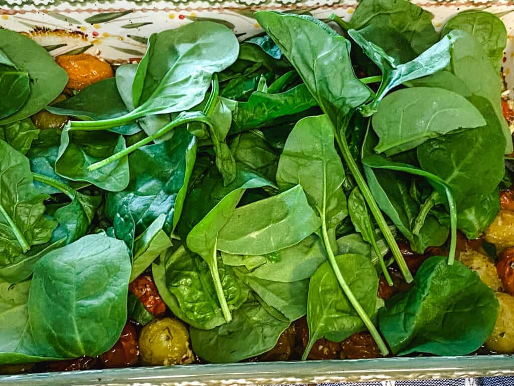 adding spinach to tomato feta pasta